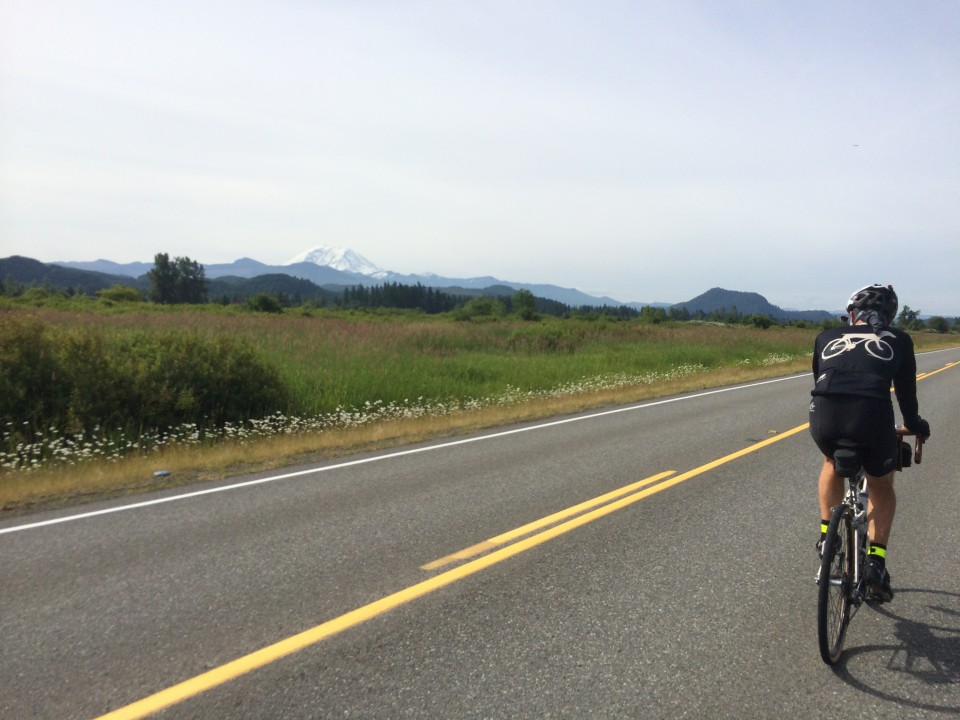 Drewski rides by with Mt. St. Helens in the distance. Photo: D. Banks